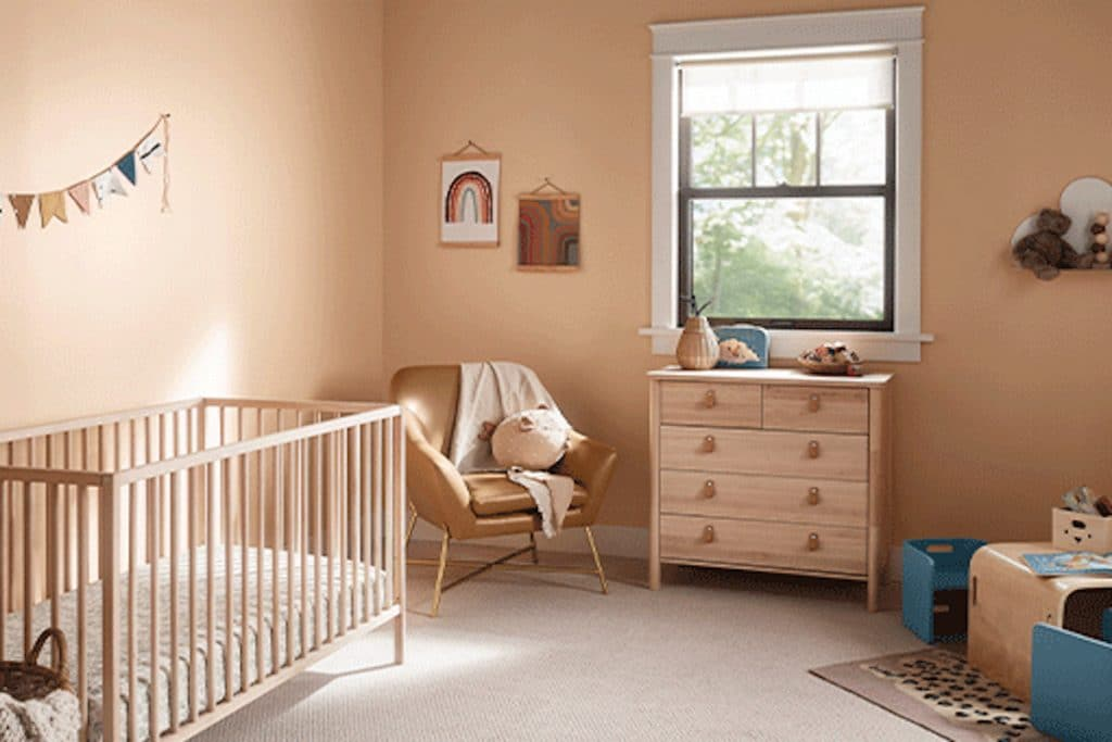 A nursery with soft apricot walls and light-colored wooden furniture.