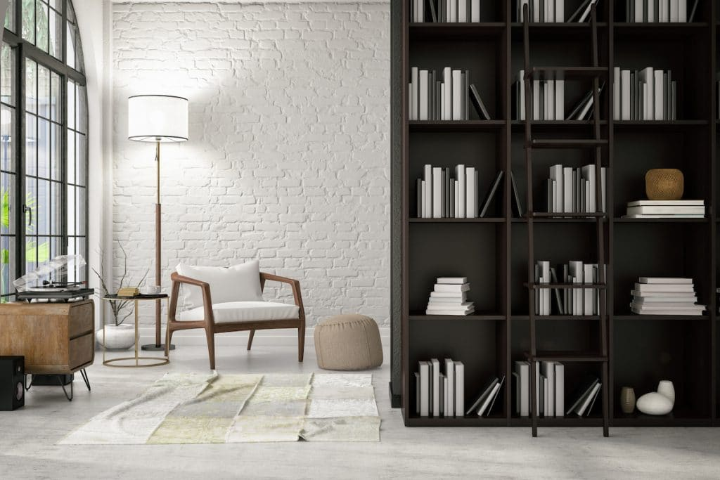 A bookcase partitioning off an area of a room.