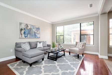 A neutral colored living room with large artwork piece behind sofa.