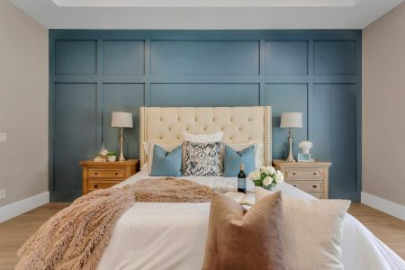 Blue accent wall behind a cream-colored headboard in a master bedroom