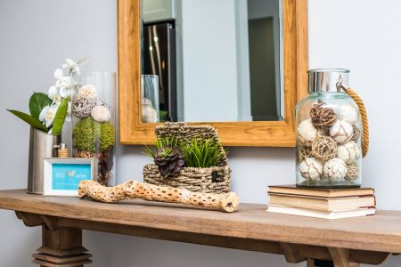 Close up of console table with vignette and wooden mirror above.