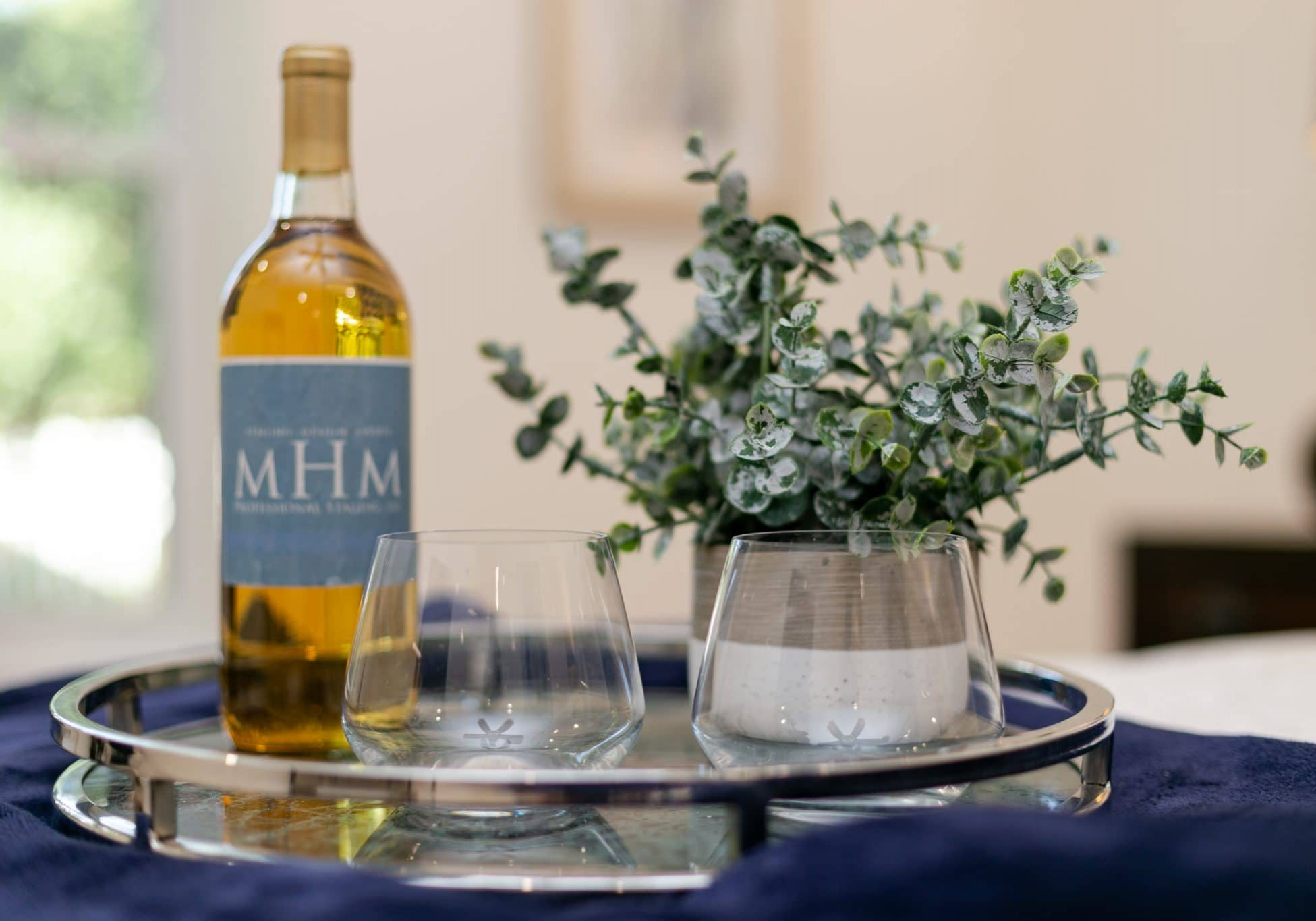 MHM Professional Staging wine bottle, glasses, and plant on a tray
