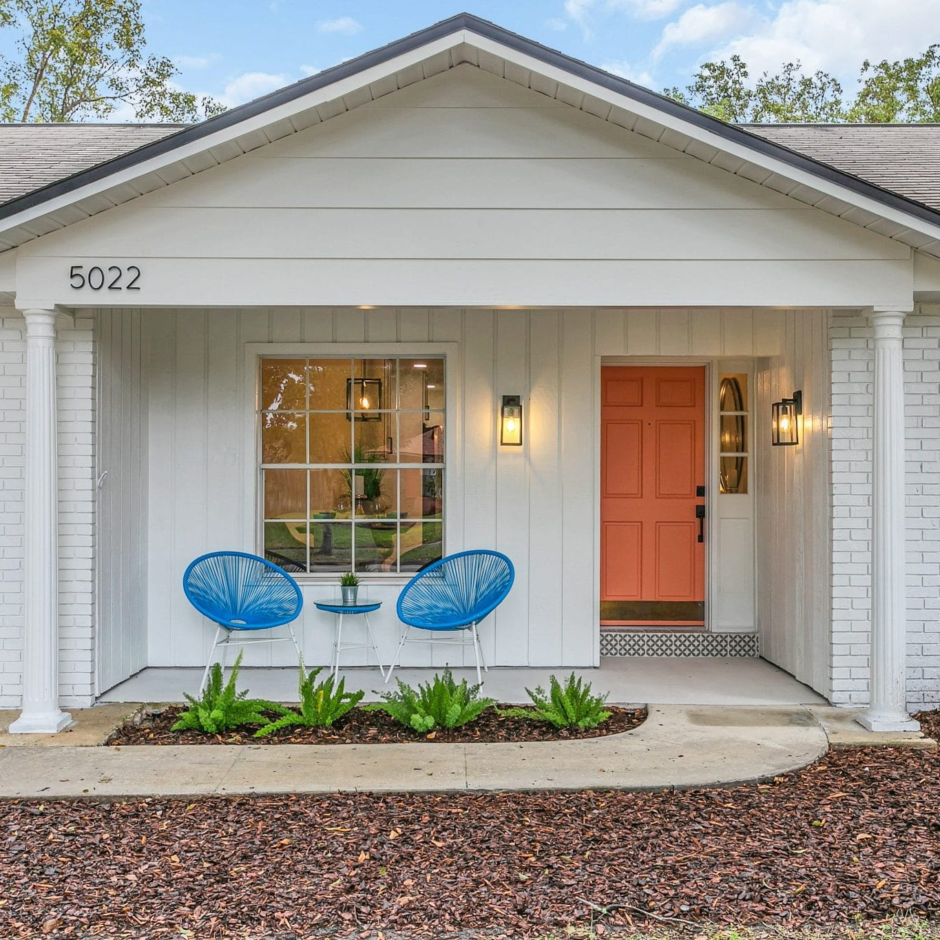 Orlando Home Staged by MHM Professional Staging with orange front door and outdoor blue chairs