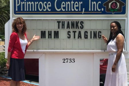 Primrose Center staff standing next to a marquee sign that reads,