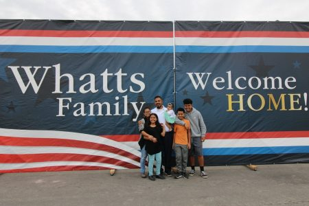 The Whatts family stands in front of a Welcome Home sign
