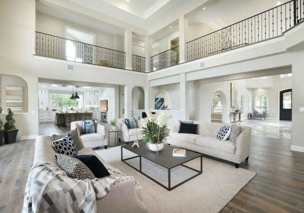 Orlando Home Staging by MHM Professional Staging - Large two-story white living room staged with white and cream-colored couches and a coffee table with large white orchid centerpiece