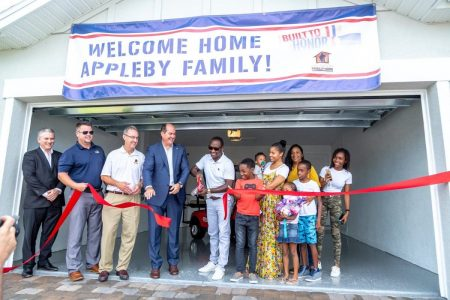 Appleby family cutting the red ribbon in front of their new home donated by PulteGroup's Built to Honor program