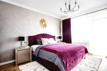 Gray bedroom with Dynamo colored headboard, Dynamo colored throw blanket, and gold accent mirror hanging above the bed