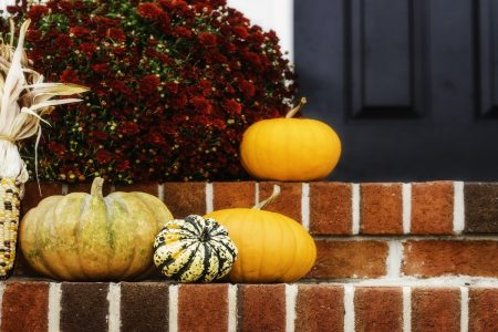 Close up of home entryway with season flowers and pumpkins.