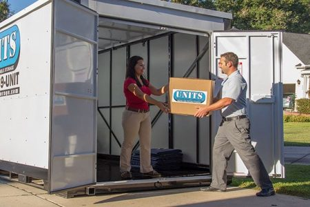 A woman and man holding a box in front of a UNITS storage container.